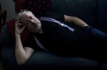 Leif GW Persson ligger i en soffa.