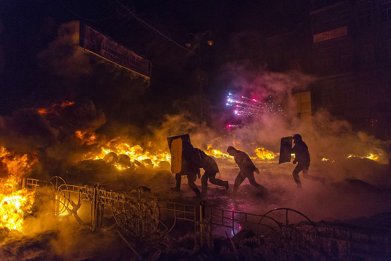 Bilden föreställer aktivister som springer över Självständighetstorget i Kiev, under revolten i Ukraina som ledde till president Janukovytjs fall.